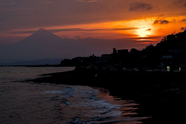 Scenic View Of Beach With Silhouette Mt Fuji In Background During Sunset
