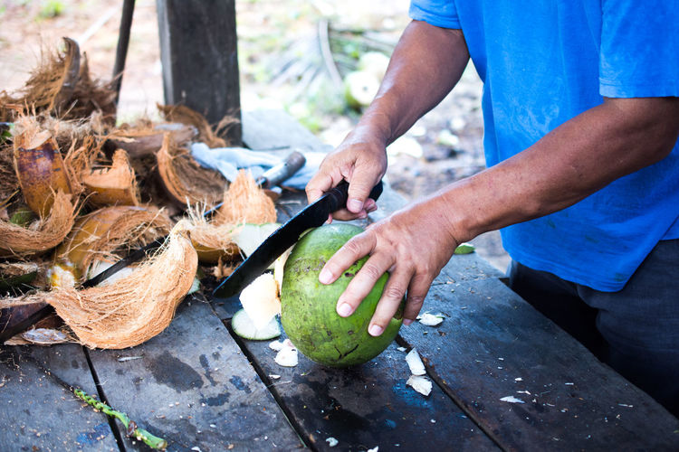 Close-Up Of Man Cutting Coconut