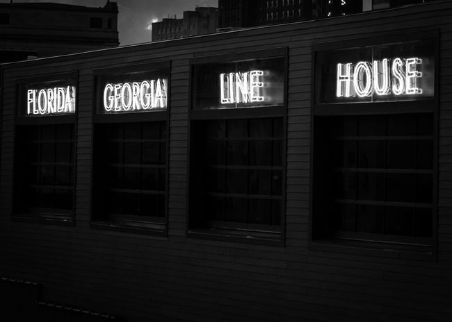 FGL House is Downtown Nashville. Architecture Black Building Exterior Built Structure Capital Letter Close-up Communication Direction Guidance Illuminated Neon neon life Night No People Number Open Sign Outdoors Text Western Script