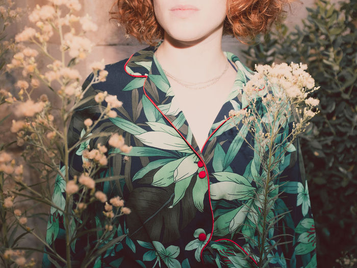 Midsection of woman standing by plants