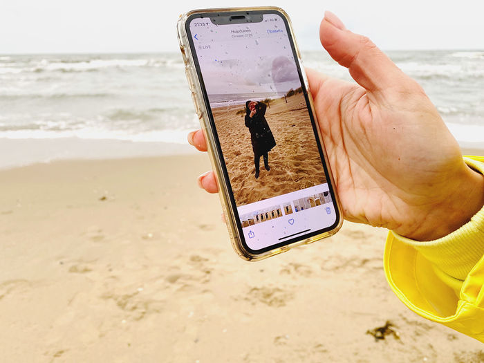 Midsection of man holding mobile phone at beach