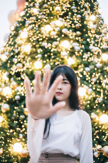 Capture Tomorrow Tree One Person Plant Front View Lifestyles Holiday Christmas Waist Up Illuminated christmas tree Real People Young Women Portrait Women Celebration Young Adult Decoration Leisure Activity Hand Hair Hairstyle Christmas Ornament Outdoors Beautiful Woman