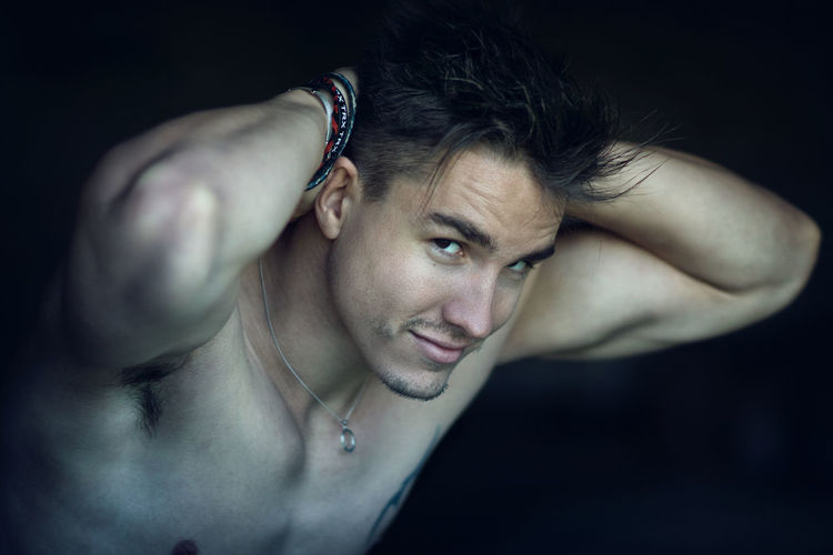Close-Up Of Shirtless Young Man Against Black Background