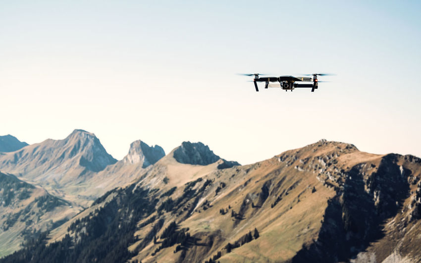 View of drone flying against mountains and clear sky