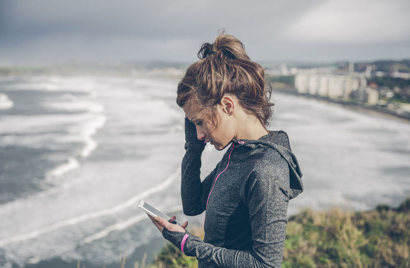 Woman using mobile phone while standing on sea shore