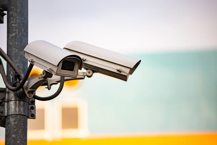 Close-up of security camera on pole against sky