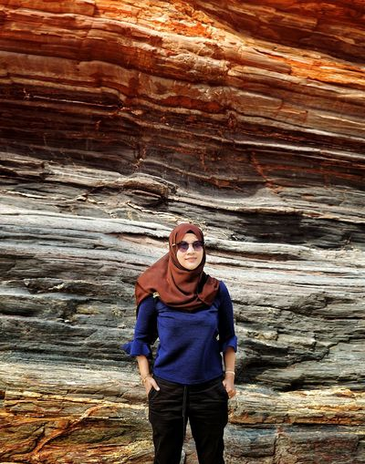 Portrait of young woman standing against rock formation