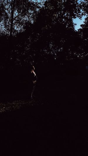 Side view of woman standing against trees at night