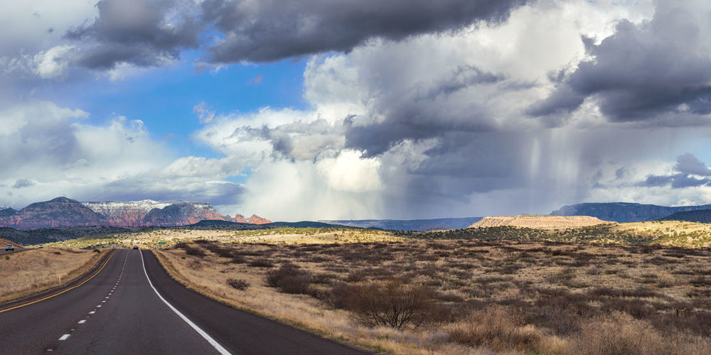 Panoramic view of country road against cloudy sky