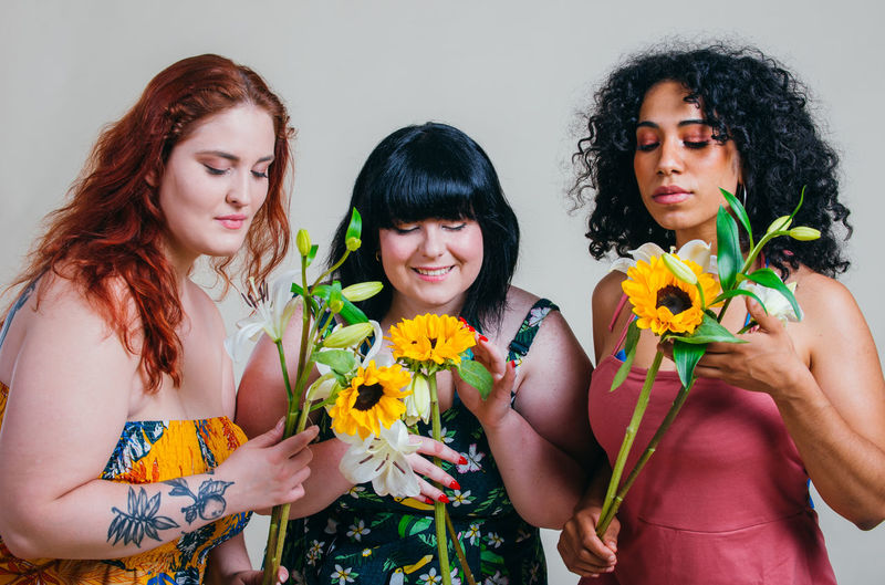 Smiling young women holding flowers against white background