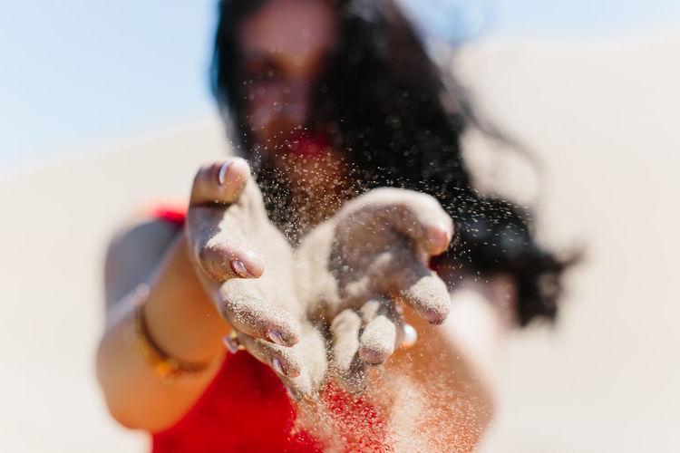 Woman Throwing Sand At Desert