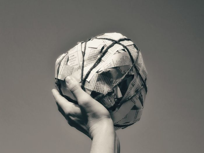 Cropped Hand Holding Paper Ball Against Sky