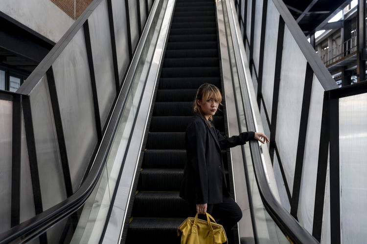 Woman standing on escalator