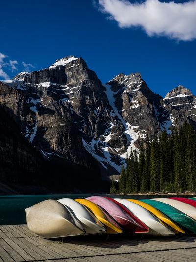 Kayaks on dock against mountains against sky