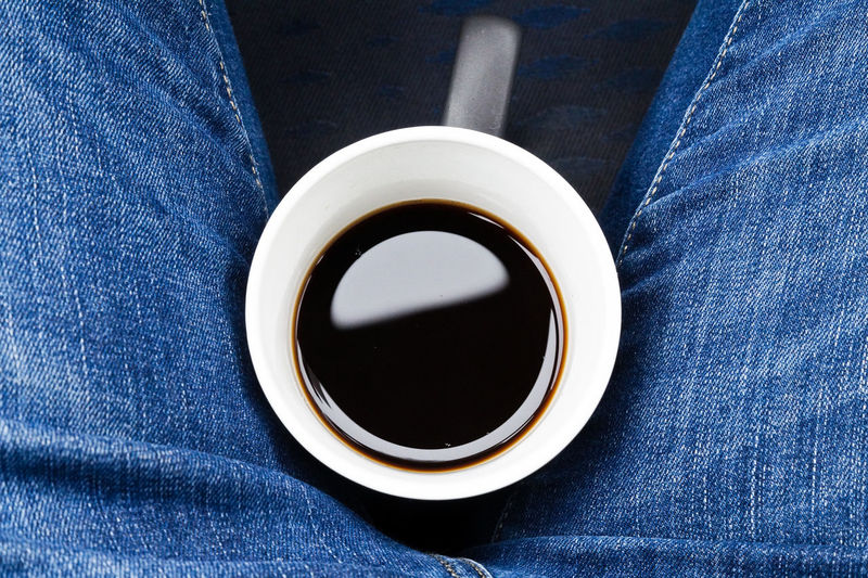 Directly above shot of black coffee between person lap