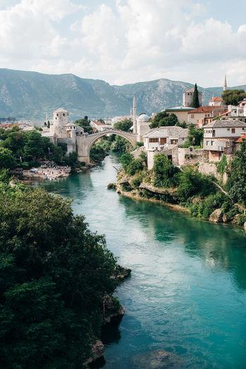 River Amidst Buildings Against Sky