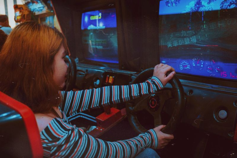 Girl sitting and playing a racing game on arcade