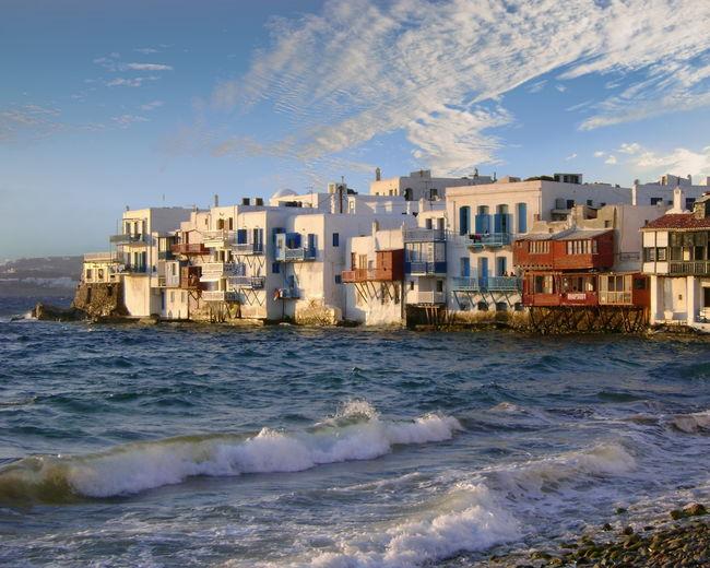 Sea By Houses Against Sky