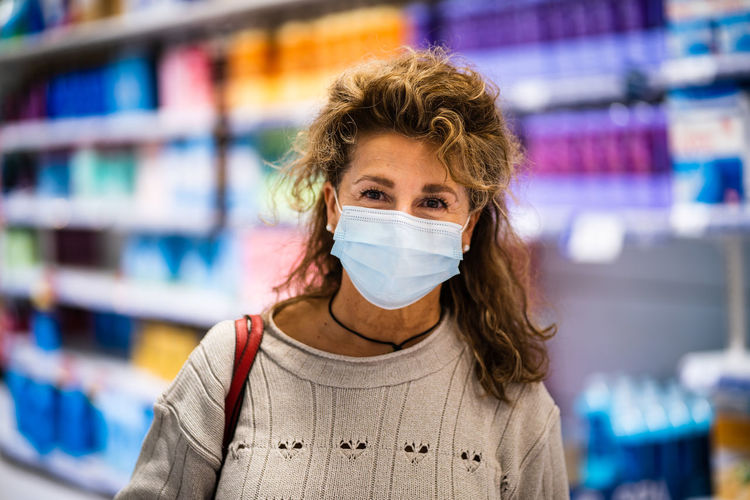 Portrait of woman wearing mask standing in store