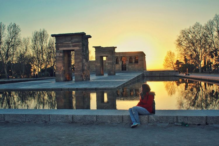 Woman sitting by pond at temple of debod during sunset
