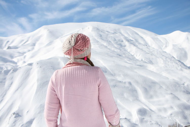 Rear view of woman standing against snow capped mountain