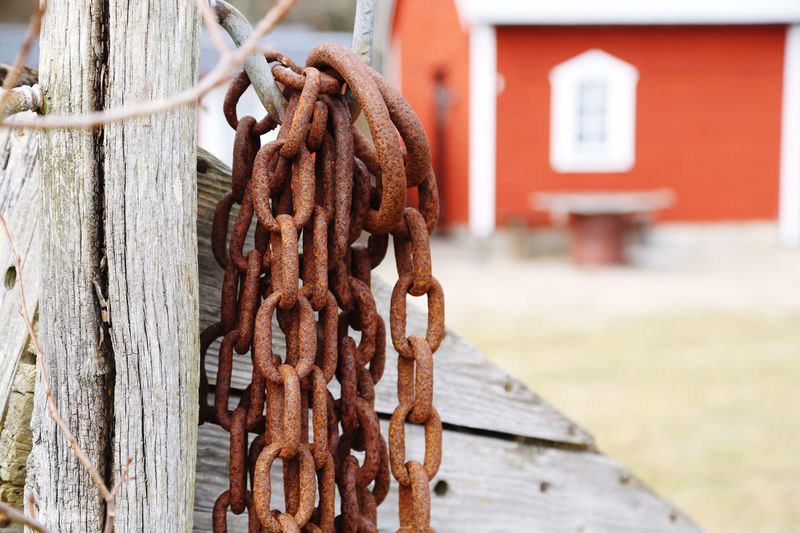 Close-up of rusty metal chain on wood