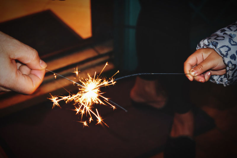 Cropped hands holding sparklers at night