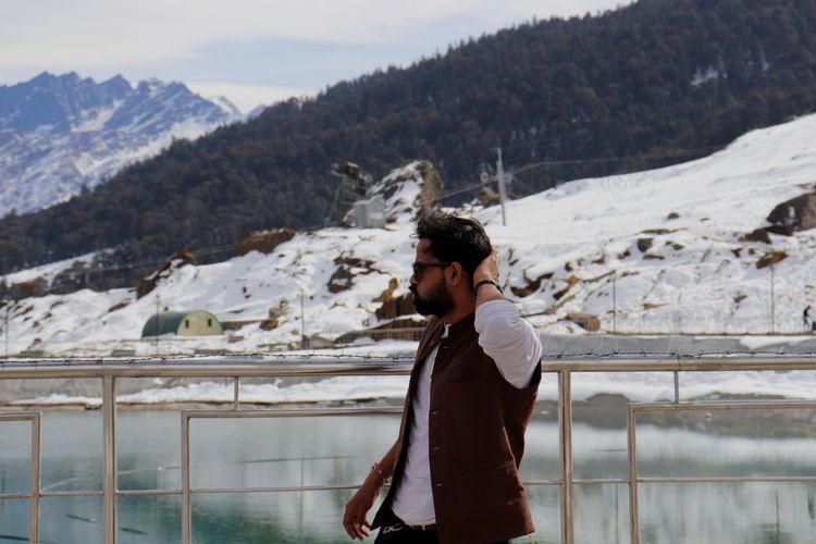 Man Walking By Lake Against Mountains