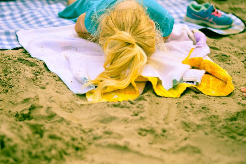 High angle view of child lying on sand