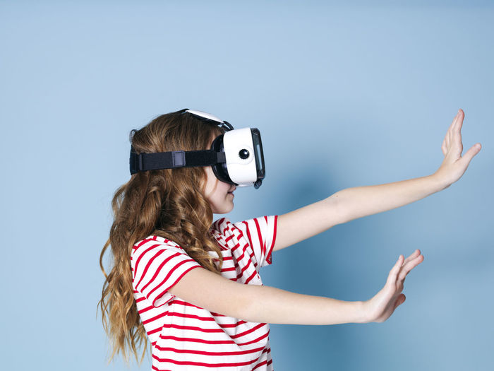 smiling positive girl wearing virtual reality glasses goggles headset, vr box. connection, modern, new generation, concept. girl trying to touch objects in virtual reality, studio shot on blue background Cyberspace Goggles Virtual Glasses Simulation Girl Entertainment Future Generation 360 3D Box Design Business Fun Joyful Gaming Game Electronic Futuristic Blue Copy Space Experience Young Human Woman Model Visual Viewer Video Film Look Observe Learn Pupil School Funny Technology Technical University  Visions Safety Glasses Glass Cool Female One Translated With Www.DeepL.com/Translator Women Indoors  Headshot Child Leisure Activity One Person Portrait Girls Studio Shot Hair Striped Childhood Lifestyles Casual Clothing Virtual Reality Simulator Waist Up Hairstyle Blue Background Human Arm