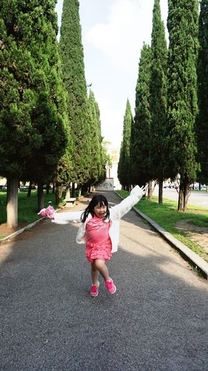 Full length of cheerful girl standing with arms outstretched amidst trees