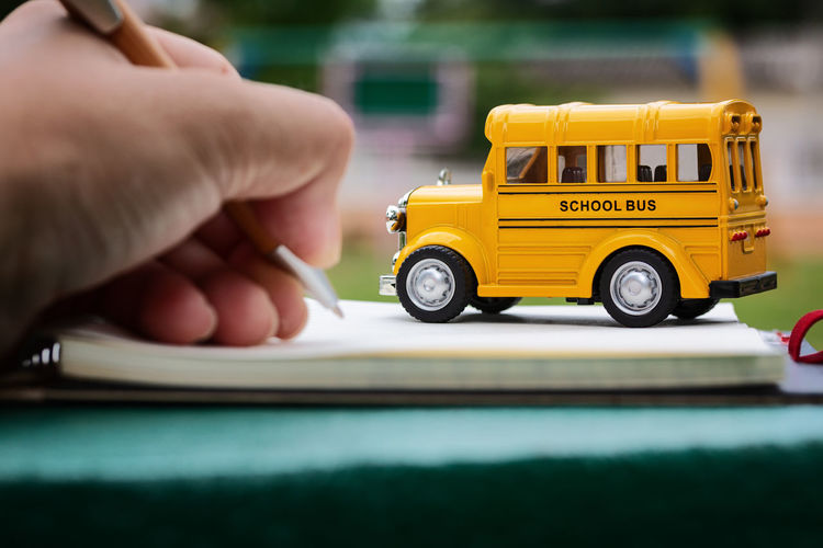 Cropped hand writing in paper by toy school bus