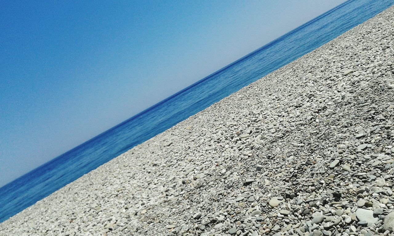 sea, horizon over water, water, beach, tranquil scene, scenics, tranquility, nature, beauty in nature, shore, blue, sand, idyllic, clear sky, day, outdoors, no people, sky, pebble beach, close-up