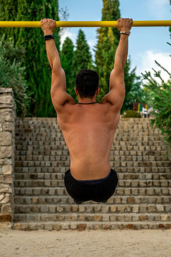Rear view of shirtless man with arms raised
