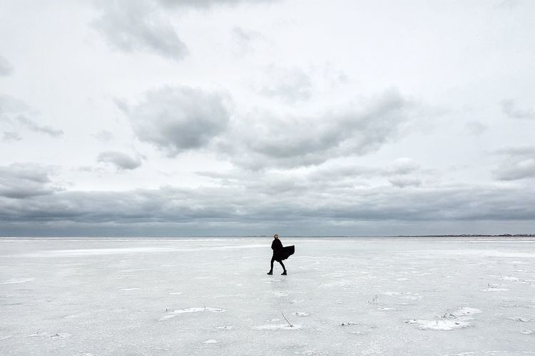 Full length of woman walking on salt flat against sky