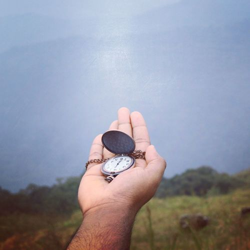 Cropped Hand Of Man Holding Pocket Watch Against Sky