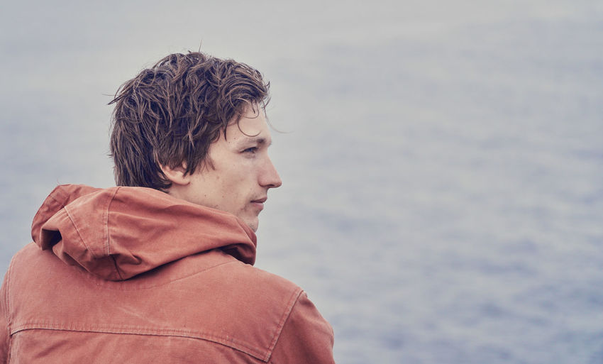 Close-up of young man looking at sea against sky