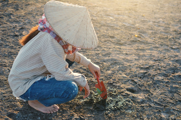 Woman Planting While Crouching On Field