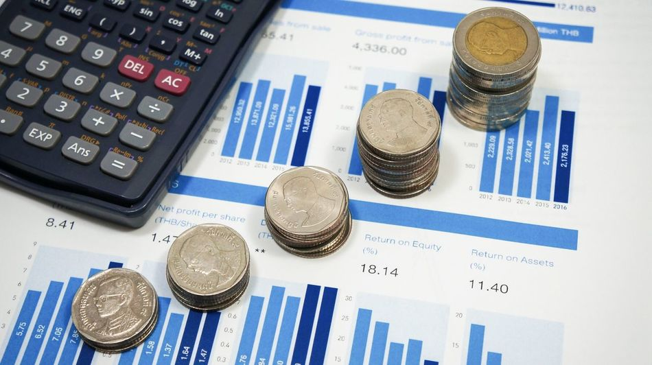 Money increase after value investor analysis financial report of stock company. Analyzing Budget Calculator Chart Close-up Coin Currency Data Day Finance Financial Figures Graph Growth High Angle View Indoors  Investment Money Heap Money Saving Increase No People Number Paper Price Tag Report Savings Technology