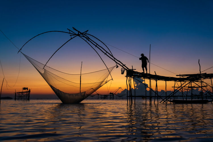 Silhouette fishing net in sea against sky during sunset