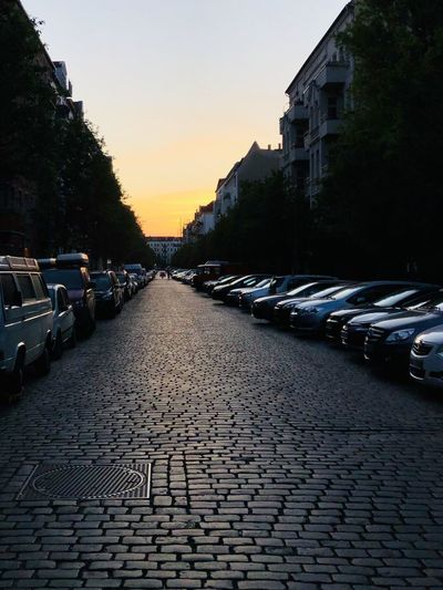 Cobblestone street amidst buildings in city during sunset