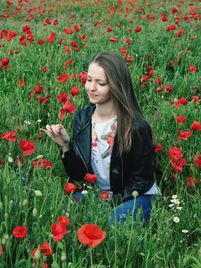 Beautiful young woman on red poppy flowers in field