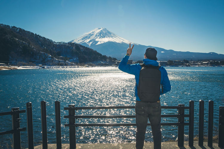 Rear view of man showing peace sign by lake against mt fuji in winter