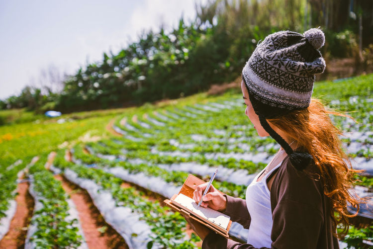 Woman wearing knit hat writing in book while standing on field