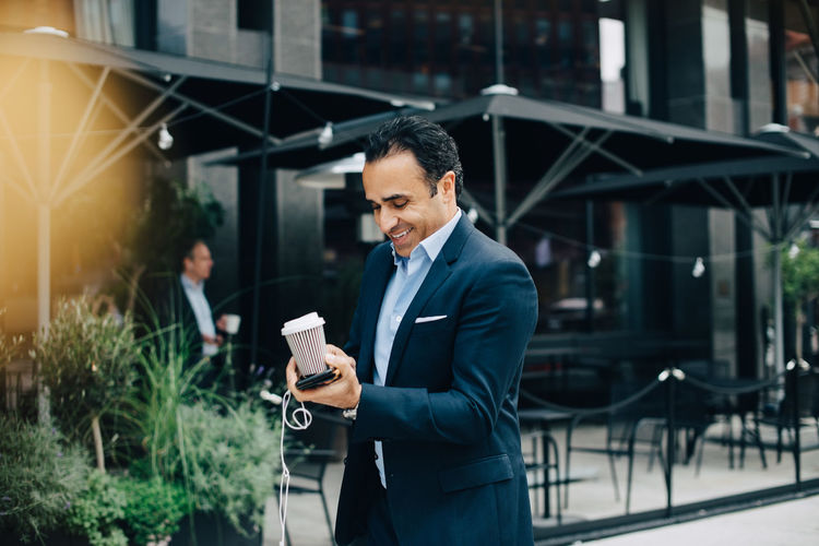 Man using mobile phone while standing at camera