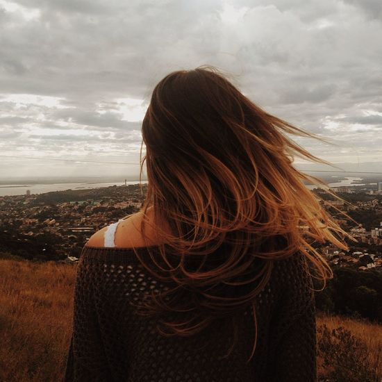 Rear view of woman overlooking urban sprawl against sky