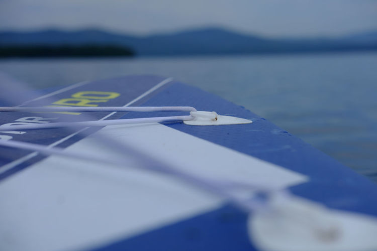 Close-up of paper on table by lake