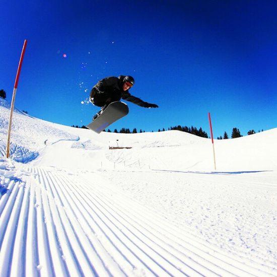 Snowboarden in Damüls bei strahlend blauem Himmel Sky Damuels Blue Snow Jump White Snowboard Schnee Snowboarding Kicker Sprung Austria Bluesky Schanze Österreich Fun Snowboarden Air Damüls