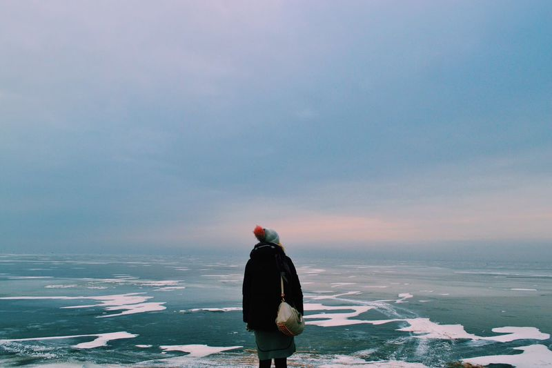 Rear view of woman looking at landscape against cloudy sky during winter
