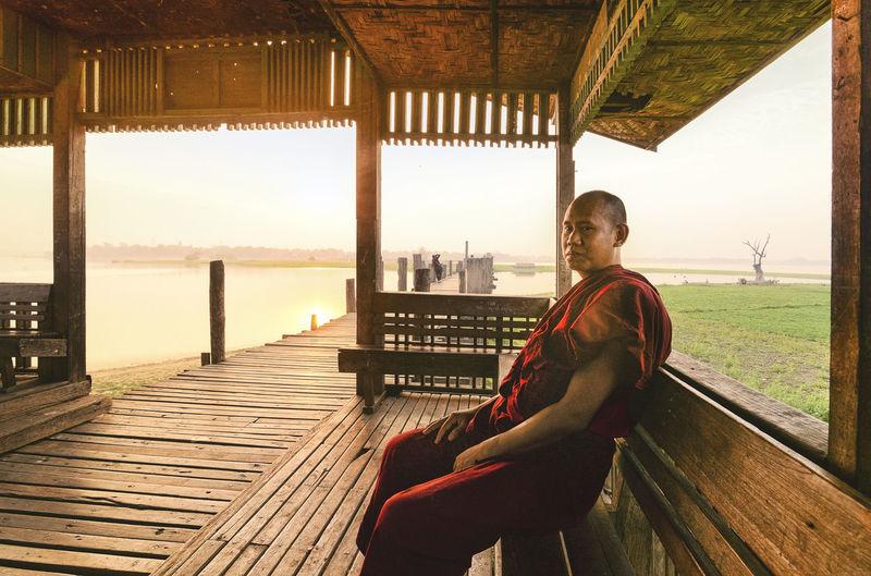 Monk Sitting On Bench At Lake